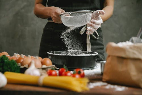 Crop anonymous chef adding flour to baking dish while making meal with eggs cherry tomatoes and spaghetti