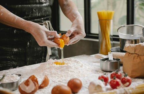 Crop anonymous person adding egg in flour while cooking pastry for recipe with cherry tomatoes and spaghetti
