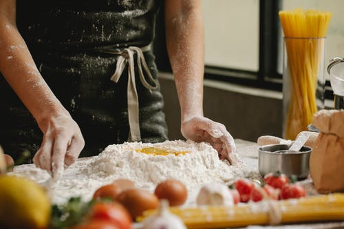 Cook preparing dough with flour and eggs