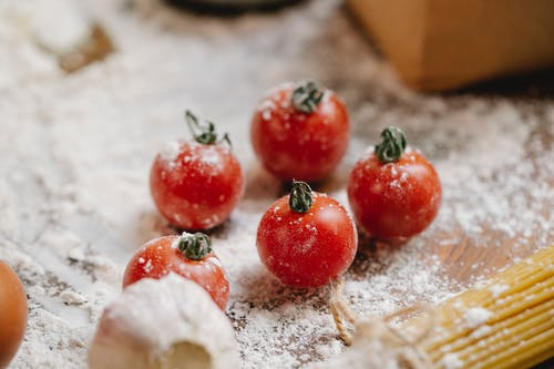 From above of ripe red cherry tomatoes with garlic and raw spaghetti on wooden table with flour