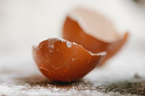 Closeup of broken eggshell placed on table with scattered flour in kitchen for cooking