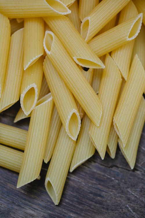 Raw pasta on wooden table for Italian dish