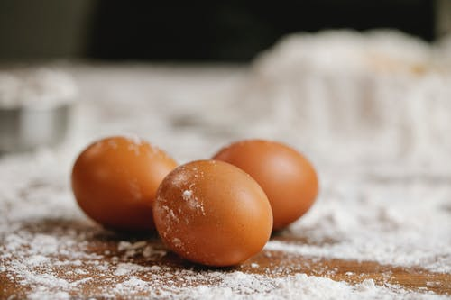 Raw eggs placed on wooden table with flour for cooking process in kitchen