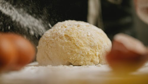 Dough with flour and eggshell in kitchen