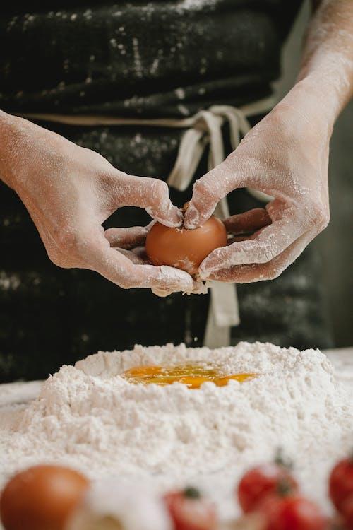 Persona Sosteniendo Huevo Marrón Con Polvo Blanco