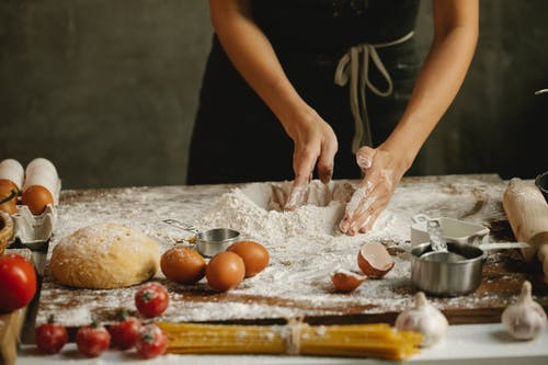 Woman making dough on table