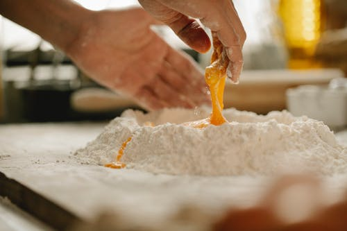 Chef mixing egg with flour for making dough