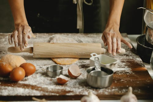 Chef rolling dough on table in kitchen
