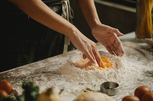 Persona Sosteniendo Polvo De Naranja Sobre Una Tabla De Cortar De Madera Marrón