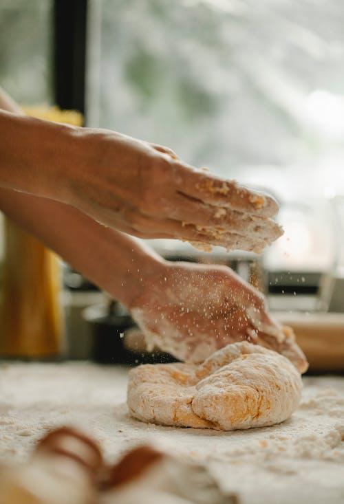 Persona Sosteniendo Pan Con Polvo Blanco