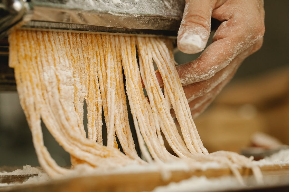 Crop unrecognizable chef preparing spaghetti from uncooked dough with flour using pasta rolling machine in kitchen