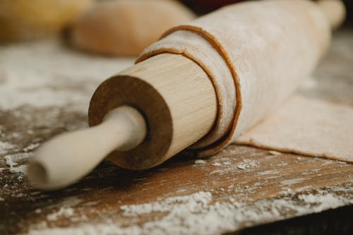 Thin dough on rolling pin on messy table