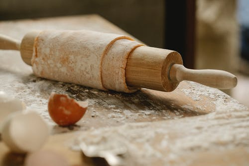 Rolling pin wrapped with uncooked sheet of dough placed on wooden table sprinkled with flour near eggshells in kitchen on blurred background