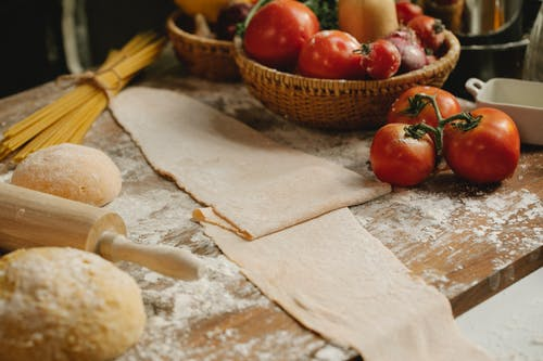 Raw dough on table with tomatoes