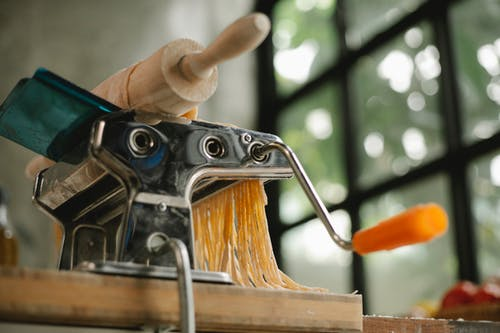 From below of modern stainless pasta maker equipment with cut raw dough placed on wooden table in kitchen on blurred background