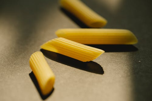 Raw penne rigate on dark surface