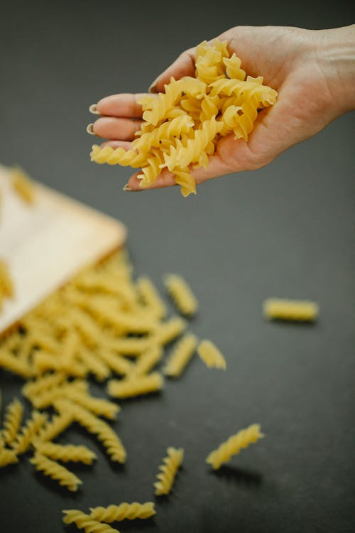 Anonymous woman dropping fusilli pasta on table