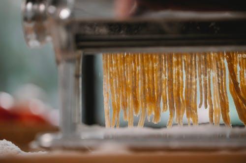 Process of cutting pasta with machine on kitchen
