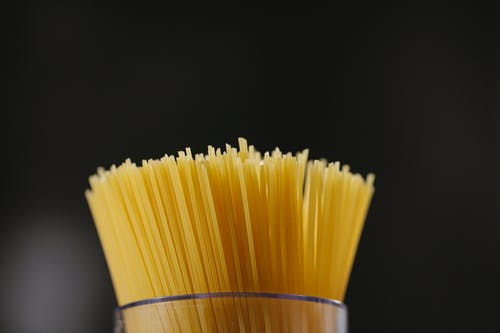 Low angle of pile of uncooked spaghetti placed in glass jar against black background