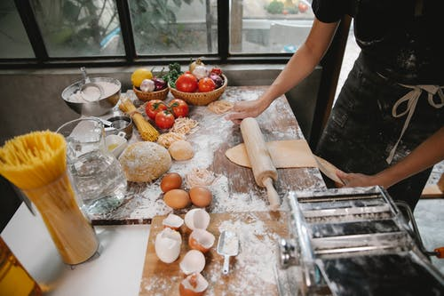 From above of crop anonymous person cooking pasta on table with eggshell and uncooked spaghetti with vegetables