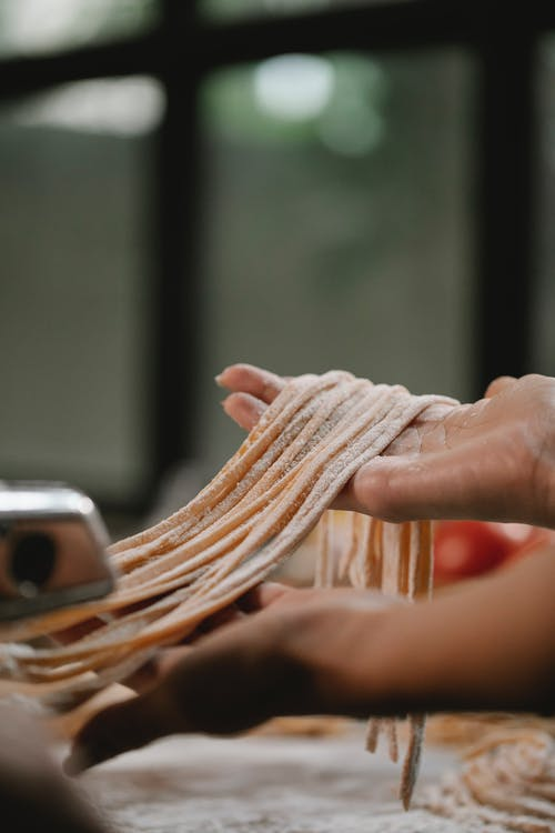 Crop anonymous female preparing pasta for cooking while using pasta machine on blurred background