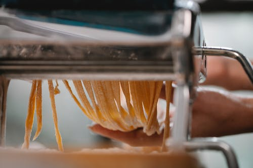 Crop anonymous female making fresh thin noodle while cutting dough in pasta machine