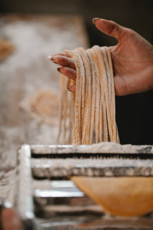 Woman with noodle made in pasta cutter