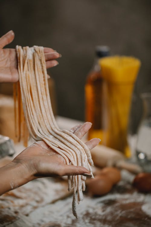 Woman demonstrating pasta covered with flour
