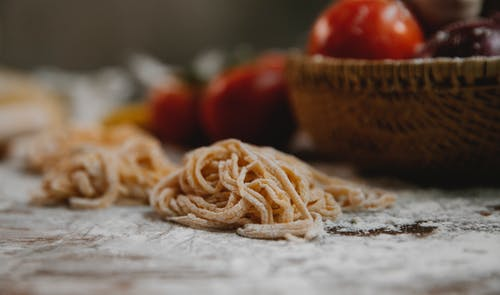 Thin spaghetti arranged with timber bowl with tomato and vegetables on table covered with flour