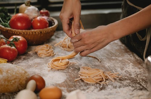 Crop anonymous female chef making homemade Italian pasta nests while cooking in modern kitchen