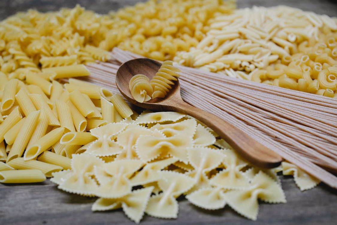 Arrangement of uncooked various pasta including spaghetti fusilli farfalle and penne heaped on table with wooden spoon