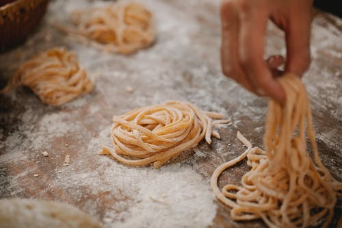 From above crop anonymous chef forming raw pasta nests on table covered with flour in kitchen