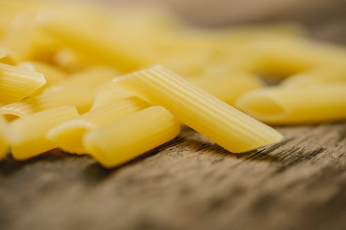 Raw penne pasta scattered on table