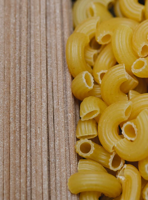 Top view composition of uncooked Italian pipe pasta and spaghetti arranged on table in kitchen