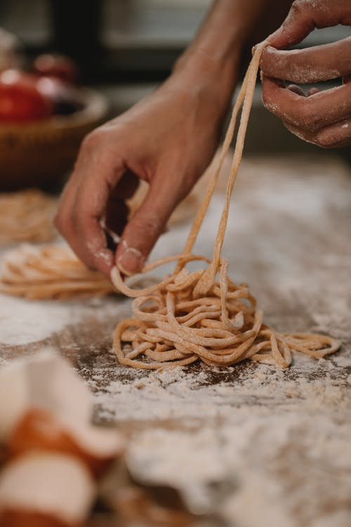 Crop anonymous chef forming Tagliatelle pasta nests on table with flour and ingredients
