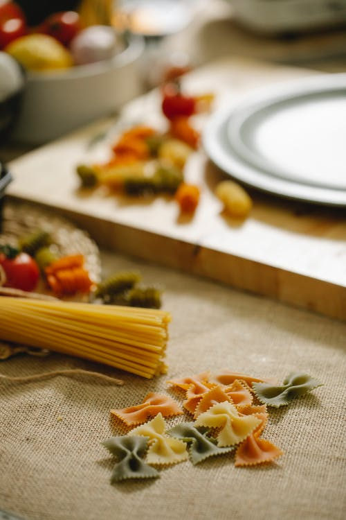 Composition of raw assorted pasta including spaghetti and multicolored farfalle arranged on table in light kitchen