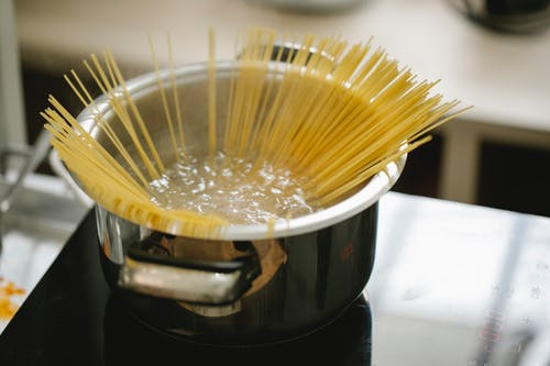 Raw spaghetti cooked in boiling water in saucepan placed on stove in light kitchen