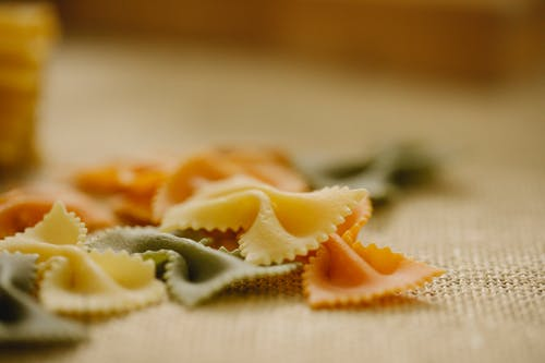 Composition of uncooked multicolored Italian farfalle pasta scattered on table in light kitchen