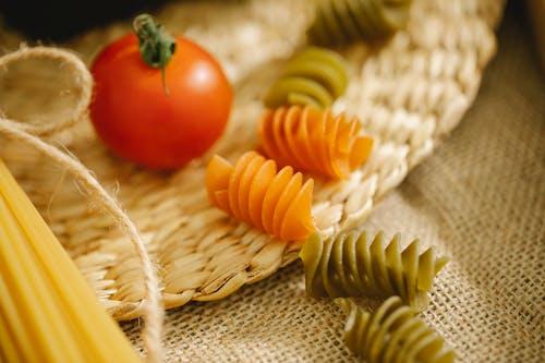 Raw fusilli pasta scattered on table near tomato