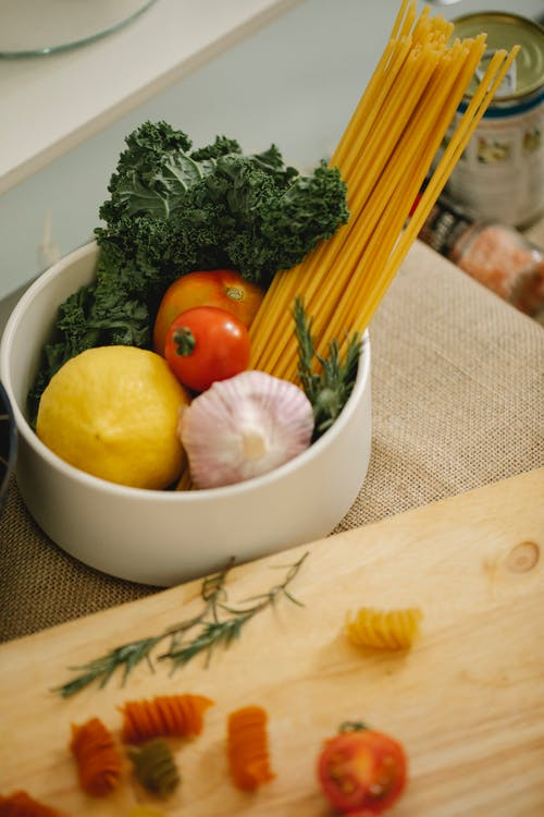 Bowl with ripe vegetables and spaghetti on table