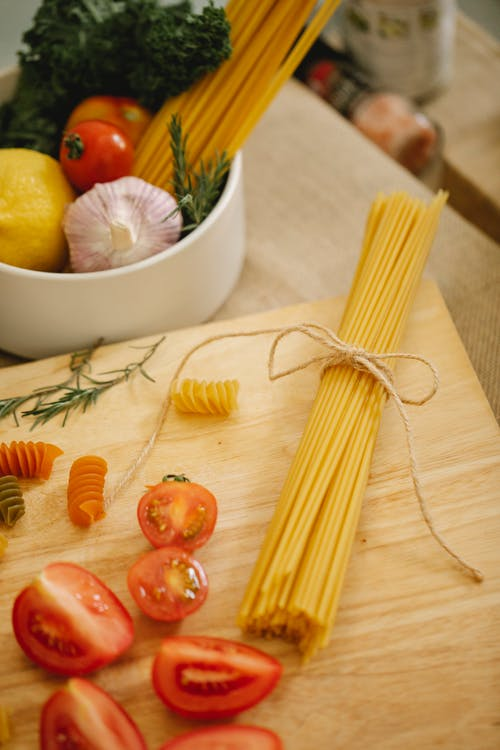 From above composition of uncooked spaghetti and cut tomatoes on chopping board placed on table near bowl with rip vegetables