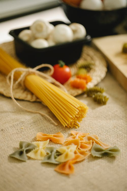 Raw pasta and mushrooms placed on table