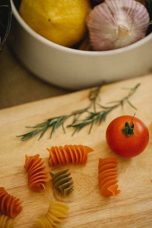 From above composition of uncooked fusilli pasta scattered on wooden board with tomato placed on kitchen table near bowl with ripe vegetables