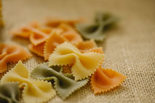 Selective focus of uncooked multicolored farfalle pasta scattered on table in light kitchen