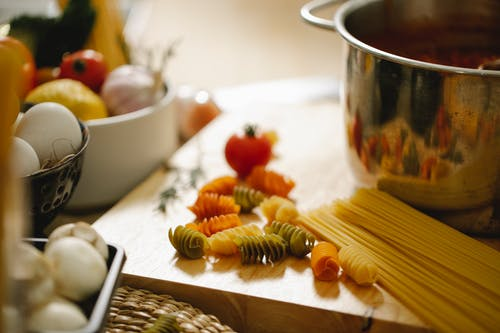 Raw pasta scattered on wooden board near saucepan in kitchen