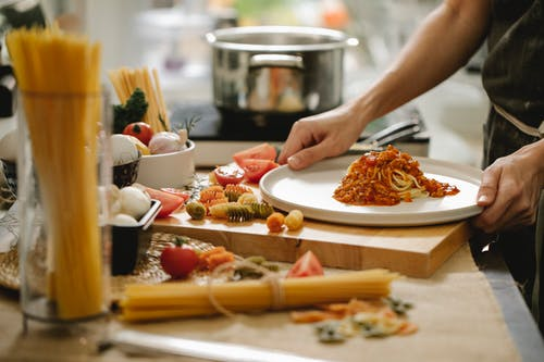Crop anonymous cook standing at table with various ingredients and cooking pasta with meat and tomatoes
