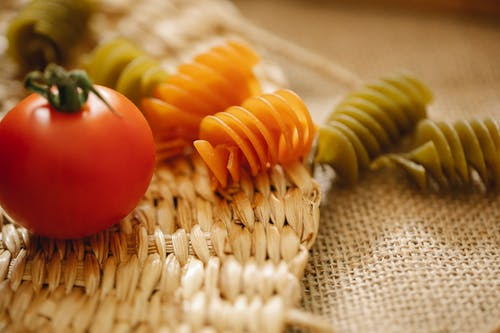 Fresh tomatoes and raw pasta on table