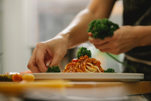 Crop anonymous housewife adding ripe parsley on delicious spaghetti with tomato sauce while cooking in kitchen