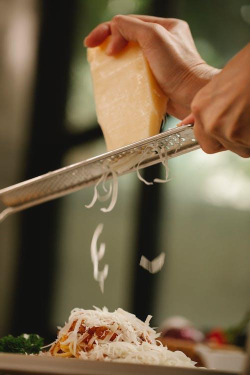 Crop unrecognizable chef grating cheese on delicious spaghetti