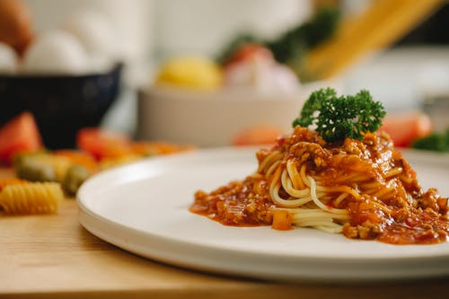 Delicious yummy spaghetti pasta with Bolognese sauce garnished with parsley and served on table in light kitchen